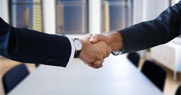 business lawyers shaking hands after closing on a case