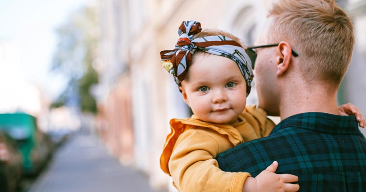 father carrying a baby daughter after getting Child support in PA