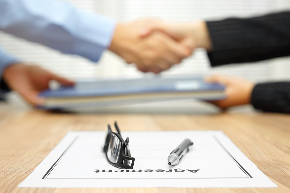 two men shaking hands signing agreement high swartz law firm
