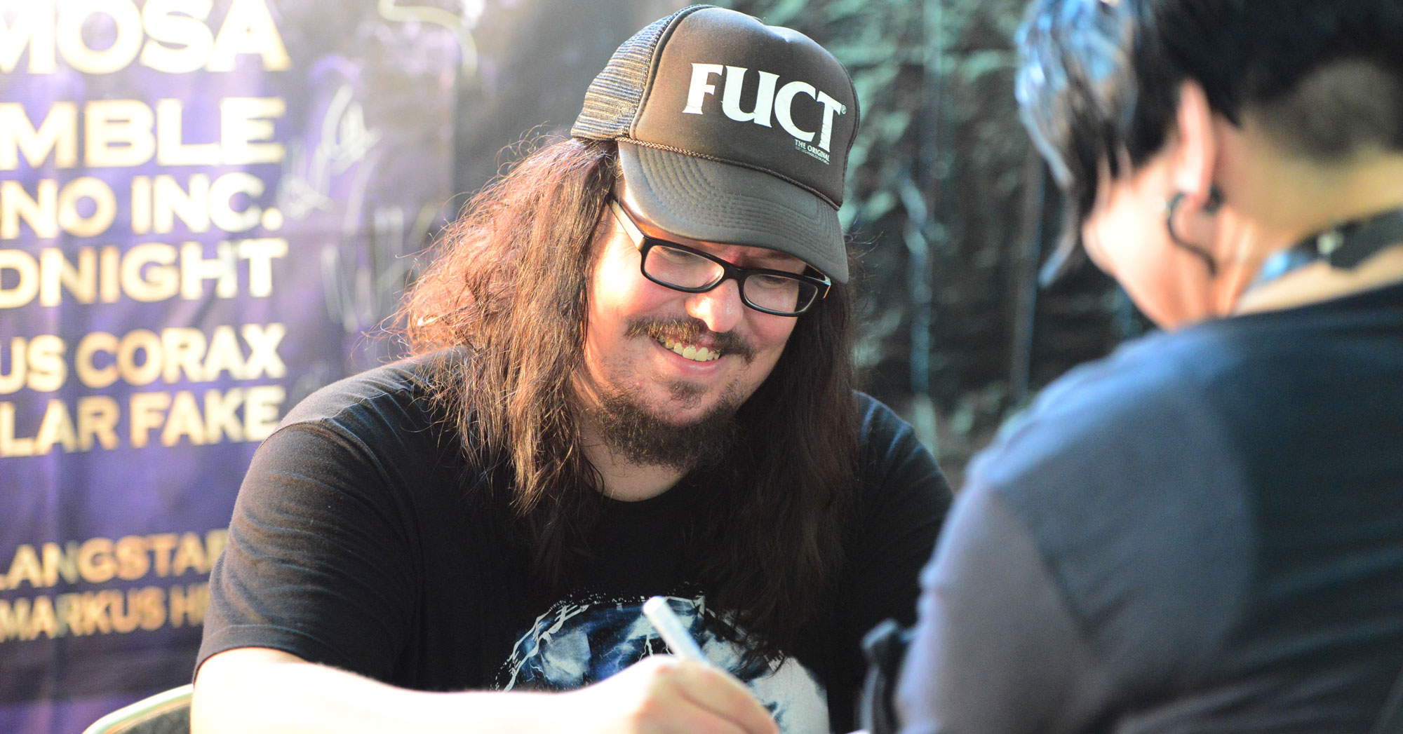 man signing autograph wearing a fuct brand streetwear clothing cap