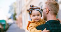 father carrying a baby receiving a child support modification from family law attorney