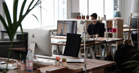 alone coworker at computer desk in office after business owner opens back up