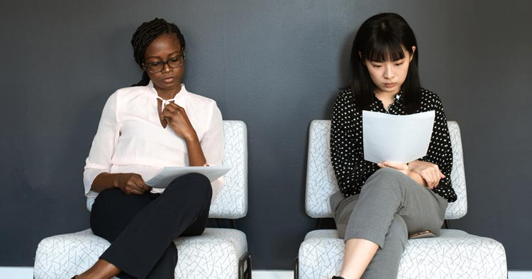 2 women reading a new workplace policy on sexual harassment