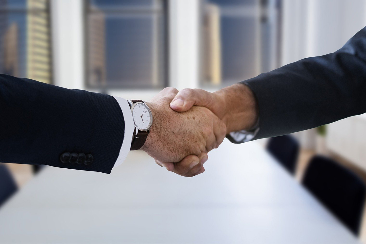 a business lawyer and corporate attorney shaking hands in a conference room after making a deal